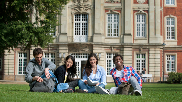 International students sit on the grass in front of the University of Bonn.